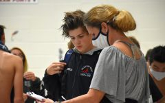"Conferencing with his coach after a meet, sophomore Jack Windler reflects on his performance from the previous event. Due to the many doubts about if there would even be a season, Windler felt grateful that he was able to swim for his school. ""Receiving the news from MSHSAA that there would be a season was relieving,"" Windler said. ""This year really gave me a chance to reconnect with the team [as]  a whole."""