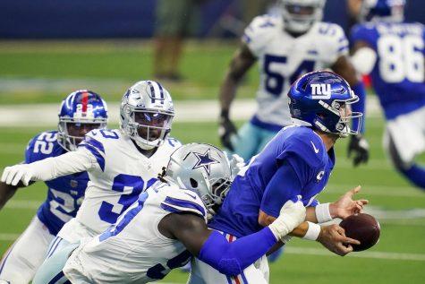 New York Giants quarterback Daniel Jones (8) fumbles as he is hit by Dallas Cowboys defensive end DeMarcus Lawrence (90) during the second quarter on Sunday, Oct. 11, 2020 at AT&T Stadium Stadium in Arlington, Texas. Cowboys cornerback Anthony Brown (30) recovered the fumble and returned it for a touchdown.