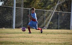 During a home game against Clayton Oct. 22, freshman Josh Seager kicks the ball away from the goal. Seager and his team played in honor of breast cancer awareness month.