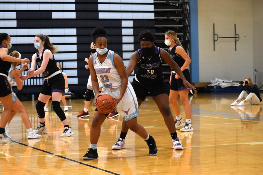 Weighing her options, junior Shemaiah Saunders aims to pass the ball and cut to the basket for a shot. This season, Saunders has had to play her games while wearing a mask.