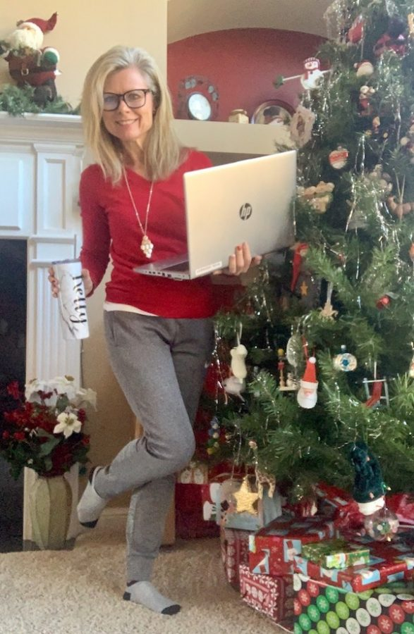 Business teacher Kelly Kennedy smiles with her laptop in preparation for a day of virtual teaching.