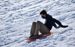 "Flying down a snow-covered hill on a bright orange toboggan, sophomore Grant Kilpatrick sleds during his Competitive Sports and Games class Feb. 18. Due to the snowstorm earlier in the week, physical education teacher Tommie Rowe brought the students outside to sled for half the class period. ""When Coach Rowe first told us we were going to get to go sledding, I was surprised because that's not something that I would think of doing during a class,"" Kilpatrick said. ""After my first few times going down the hill, normally I tried going down while standing. I tried this several times, but only getting about halfway down the hill before falling and rolling down the rest of the way. The funniest part about sledding for me was [when] we would lose control and the sled would flip. [My favorite moment was] just being able to try doing different things and have time to laugh and interact with classmates."""