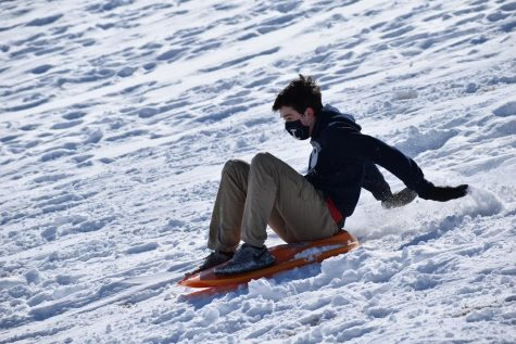 "Flying down a snow-covered hill on a bright orange toboggan, sophomore Grant Kilpatrick sleds during his Competitive Sports and Games class Feb. 18. Due to the snowstorm earlier in the week, physical education teacher Tommie Rowe brought the students outside to sled for half the class period. ""When Coach Rowe first told us we were going to get to go sledding, I was surprised because that"
