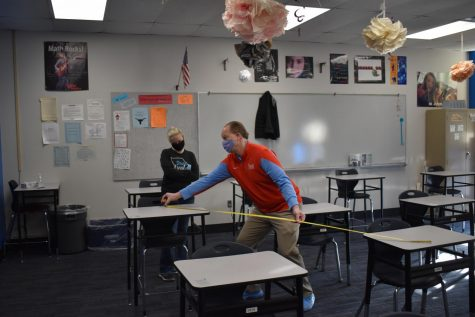 """Principal Jeremy Mitchell measures the distance between desks to aid in contact tracing. After measuring the desks, Mitchell gave the information to Assistant Principal Kate Piffel, who used seating charts to determine close contacts. """"Dr. Mitchell measures the desks to see how far apart they are because if they are within six feet [there is a] 98% chance that those students are going to have to quarantine if theyre that close to another student,"""" Piffel said."""
