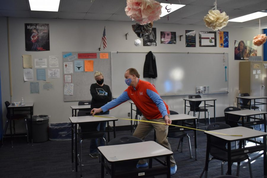 "Principal Jeremy Mitchell measures the distance between desks to aid in contact tracing. After measuring the desks, Mitchell gave the information to Assistant Principal Kate Piffel, who used seating charts to determine close contacts. ""Dr. Mitchell measures the desks to see how far apart they are because if they are within six feet [there is a] 98% chance that those students are going to have to quarantine if they"