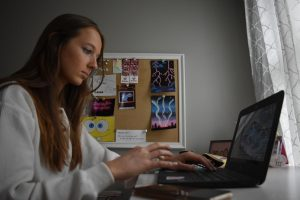 "Engaging in her online Honors English II class in the first quarter, sophomore Hannah Wagner searches to find the perfect word to add to her essay. With the first half of the school year being online, it was a different experience to do school work from her home. ""I definitely think working at home was more enjoyable because I felt more comfortable writing at home,"" Wagner said."