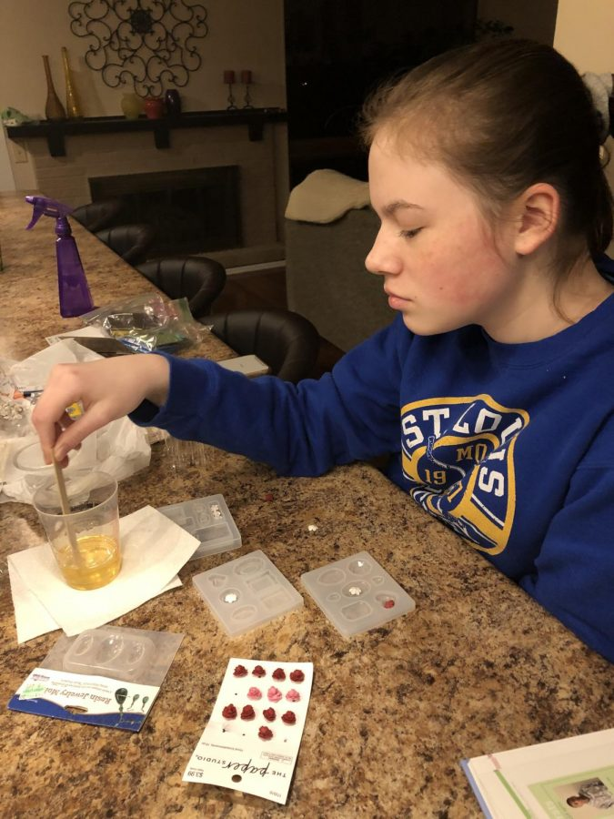 """Stirring resin, freshman Julia Thomson comes up with a new product idea. Thomson gets a lot of inspiration for Sunny Simone Co merchandise from social media. """"I'll go on TikTok or Instagram, and I will see someone have this really cool idea. It'll spark something in my mind like, 'oh, I like that color or lip gloss and that would be really cool if we did this,'"""" Thomson said."""