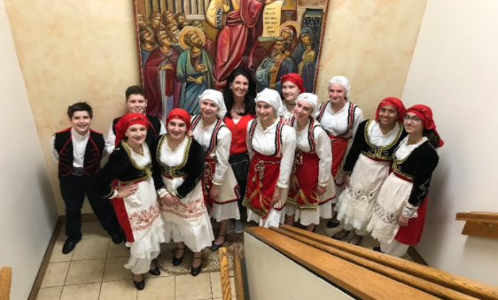 "After performing for Assumption Greek Orthodox Church, freshman Thalea Afentoullis (second to the left in the front row) poses for a picture with her class and mom. Afentoullis enjoys hanging out backstage before and after performances with her classmates and friends. ""Whenever we are not dancing, we are always backstage because we have to be ready, and we have our own dressing rooms. I just remember there being so many fun stories and we would all just eat together and be really funny,"" Afentoullis said."