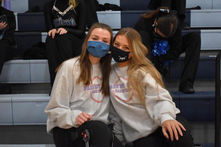 "Cheering on their fellow poms teammates, sophomores Allie Byergo and Cameron Chandler attend a varsity boys basketball game Jan. 8. Because of their injuries, Byergo and Chandler were not able to participate in any dancing. ""It's actually pretty fun to get to go to the games since not a lot of people can right now because of COVID-19,"" Byergo said. ""Ever since I've been injured, even though I haven't been able to dance, it's been really good to still be a part of the team and still be able to wear poms clothes and go and represent at games."""