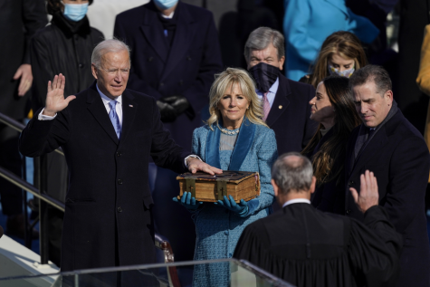 President Joe Biden takes the oath of office from Supreme Court Chief Justice John Roberts as his wife, first lady Jill Biden, stands next to him during the 59th presidential inauguration.