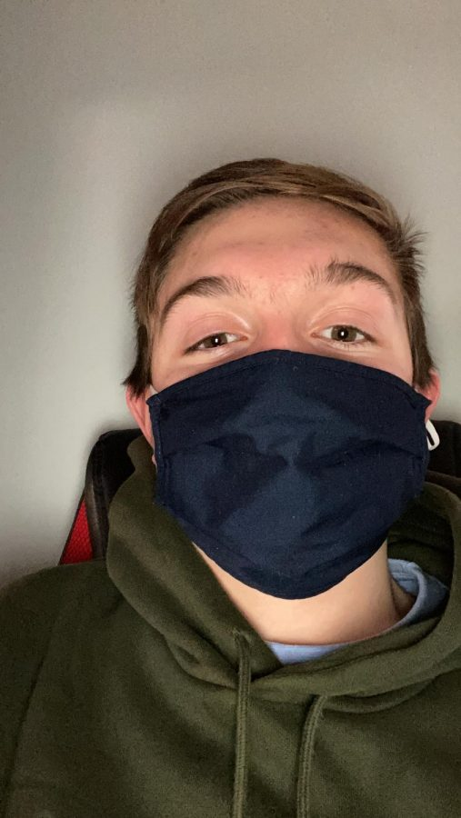 Freshman Harrison Beck poses for a picture wearing his mask.