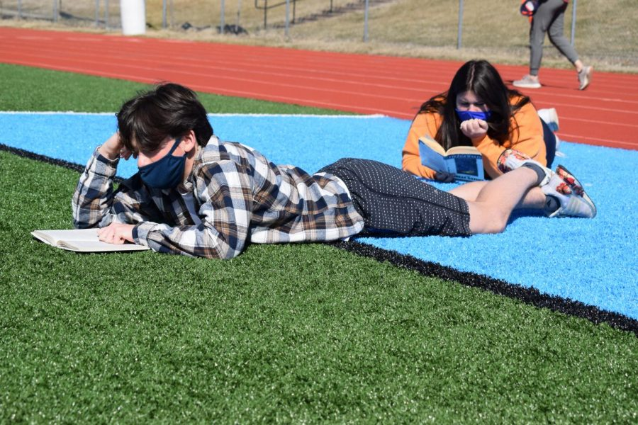 During third hour on Tuesday, junior Matt Givens reads on the football field during his English III class. Givens spent the time catching up on