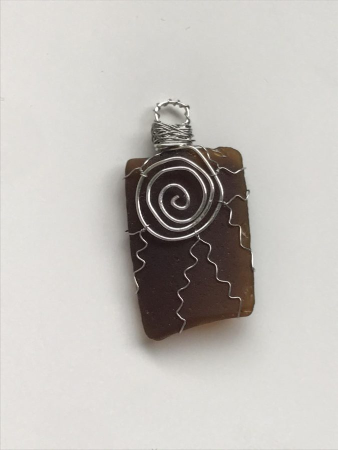 Will Be For Sale: Brown Sea Glass Pendant - One piece that was frustrating was the sun on brown sea glass, Gleason said. Although I really like the way it turned out, the wire kept springing back up and not staying in place. To deal with that, I put on good music and try to stay positive. Sometimes I have to restart, but usually, I can figure it out. Once I finished it, it ended up being one of my favorite pieces.