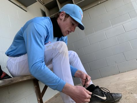 "Preparing for baseball tryouts, senior Jack Meert ties the laces of his cleats. Meert is back after being cut a year ago. ""I"