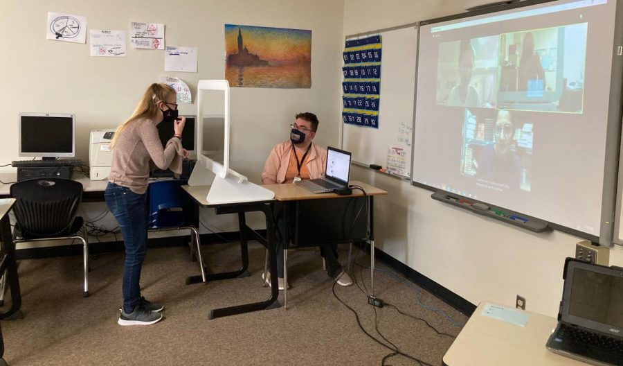 """Speaking to an in-person student, Special Education teacher Zack Jodlowski works to teach both his in-person and virtual students. Jodlowski's class was made up of deaf, Deaf and hard of hearing students. """"I think it's important for people to know there's a wide range of people involved in our community,"""" Jodlowski said."""