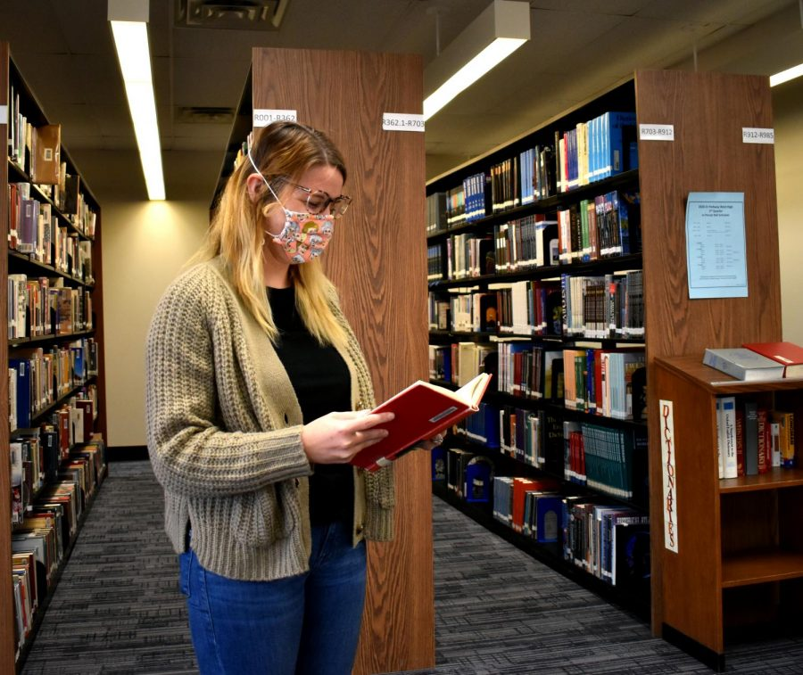 "Wearing a cardigan and blue jeans, librarian Lauren Reusch reads a book in the library. Reusch realized she typically wore the same few pieces of clothing, and has since committed to not buying new clothes for six months. ""You know your favorite pieces that make you feel good,"" Reusch said. ""The majority of the time I spend at home or with family I wear sweats."""