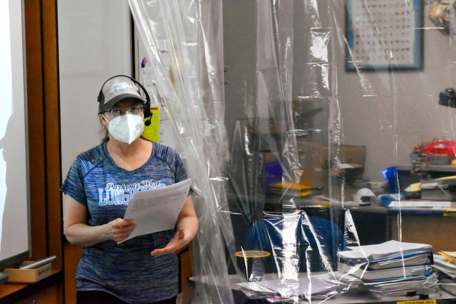 """Teaching behind a clear shower curtain, biology teacher Sally Soulier focuses on teaching her students while maintaining social distance. Soulier suffers from hearing loss and had difficulty hearing students through their masks. """"It is so hard to get to know people without their faces, and students likewise can't see me smiling,"""" Soulier said."""