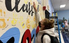 Reaching her hand up the wall in the cafeteria, senior Bella Allgeyer places her handprint among the others. The senior hand wall is a long-standing Parkway West tradition.