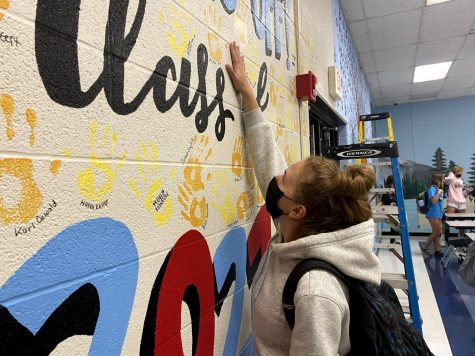 "Reaching her hand up the wall in the cafeteria, senior Bella Allgeyer places her handprint among the others. The senior hand wall is a long-standing Parkway West tradition. ""I like that the mural subtly represents everything we"