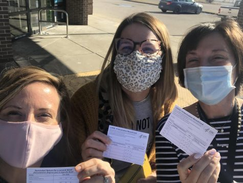 "Taking a selfie with fellow teachers, librarian Lauren Reusch displays her vaccination card. Reusch travelled with English teachers Erin Fluchel and Shannan Cremeens to Illinois to be vaccinated. ""I am most excited to go out to eat in an actual restaurant with my husband,"" Reusch said."