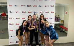 "Following a first place finish at the state tournament, the girls racquetball team celebrates their win by raising their trophy. The team participated in the JV1 bracket and hoped to move up to the varsity level next season. ""It felt good to know that we were the best team on JV1, only making us more positive we are ready for varsity next year, at least with a lot of hard work,"" junior Graci Badami said. ""I think about all the varsity players from last year, and some of my teammates from this year, and I strive to do what they do so effortlessly. I also enjoy practicing and working to get better because it's such a fun sport."""