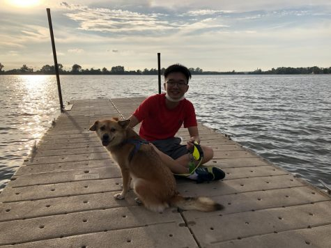 Pulling down his mask for a photo, senior Justin Xu smiles with his dog.