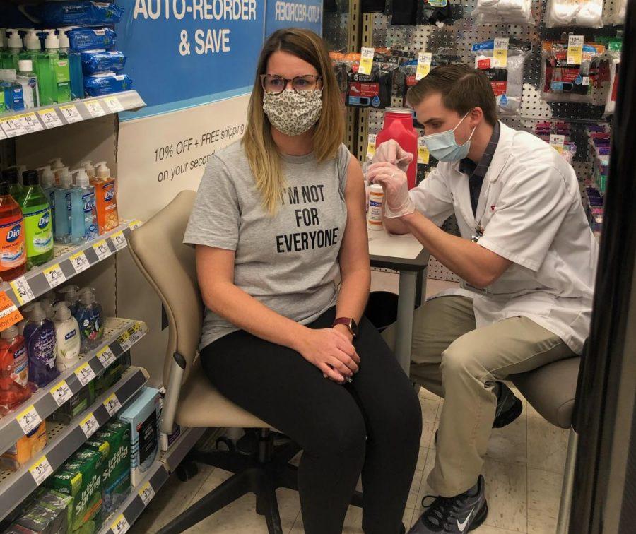 Librarian Lauren Reusch receives her first dose at a Walgreens clinic.