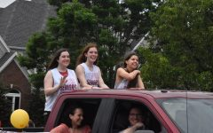Making their way through the senior parade, seniors Zoe Rutledge, Tori Fischer and Talie Ziegler smile at the crowd. Fischer has not committed to a college yet but plans on attending the University of Kentucky to study computer science and dance.