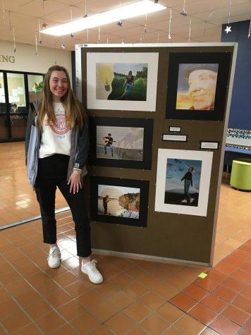 Senior Martha Wait poses next to her AP art board.