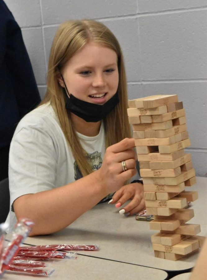 """Sophomore Abigail Wheeler plays Jenga with her friends on the last day of school after turning in their finals. Between flying twizzlers and giggling friends, Wheeler tried to ignore the distractions around her. """""""
