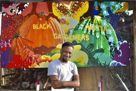 Alumnus Antajuan Adams stands smiling in front of a mural painted at New Roots Urban Farm.