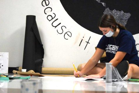 """Freshman Kora Elli makes hall decorations for homecoming spirit week on Sept. 19. Elli used Sharpies and a pencil to draw a Barbie head silhouette for the freshman hallway. """"My favorite part of floor decorations was how we all came together and worked as a team,"""" Elli said."""