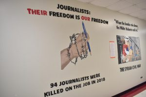 This mural, painted in the social studies hallway by the 2019 Challenges to Democracy class, commemorates 94 journalists were killed in targeted attacks, bombings and crossfire in 2018.