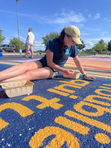 """Painting the letters of her parking spot, senior Paige Matthys-Pearce participates in painting day. Matthys-Pearce painted a starry background with a quote written in French, which says 'don't forget who you are.' """"Im happy that I got to participate in this new tradition because I think its a great way for us seniors to leave a mark here, even though the spots will get painted over at the end of the year. Pulling into the colorful parking lot each morning brings me so much joy, and all the different designs highlight how unique everyone is,"""" Matthys-Pearce said. """"Even though we sat under the sun in a hot parking lot for seven hours straight, it was a fun experience that I hope future classes will continue."""""""