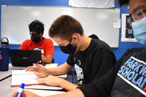 As senior Rick Biswas reads a packet, junior and Scholar Bowl Executive Captain Owen Arneson keeps track of senior Kevin Zheng