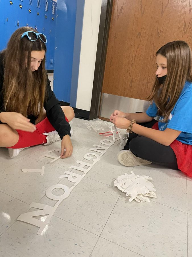 """Sporting West spirit, freshmen Sophia Licavoli and Gabbie Catlett sit in the hallway while making float decorations for the volleyball float in the parade. The two wore red tutu's to support the activities of spirit week. """"I liked sharing school spirit and seeing everyone dress-up and have fun,"""" Licavoli said. """"It was a great week."""""""