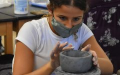 """Sculpting a Day of the Dead project in Ceramics 1, sophomore Katie Wallace creates a mug out of her pinch pot. For the assignment, Wallace carved eyes, a nose and a mouth into her mug, and later painted it in bright colors to make it unique. """"Getting to have social time, unwind and talk with my friends was my [favorite part of the] class,"""" Wallace said. """"I also liked getting to hone my creativity and get my hands dirty."""""""
