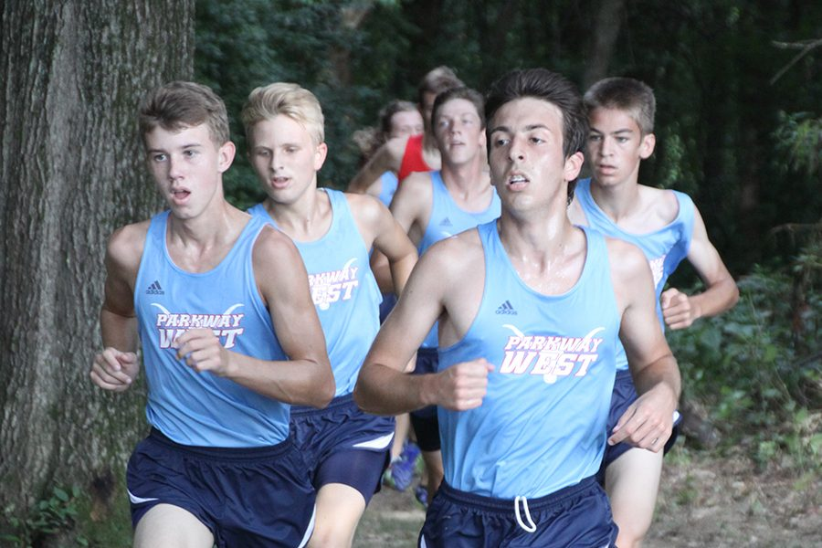 Rounding a corner in the wooded section of the Parkway Central course, junior Matyas Csiki-Fejer leads the varsity boys pack.