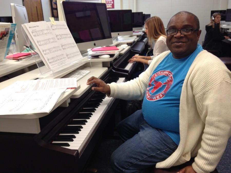Choir and Piano teacher Eric Anthony helps one of his Piano 2 students.
