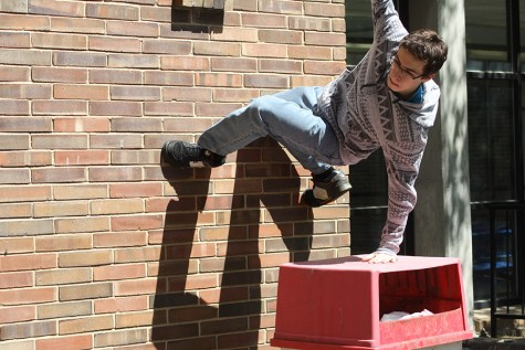 Sophomore Austin Valenti climbs a wall in the peace garden.