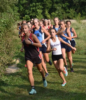 """The front pack, senior Rachel Osbourne, freshman Natalie Butler, freshman Claire Smout and junior Maggie Morse track down the leading racers in the varsity race. """"While I was running I was trying to figure out the Central girl's strategy so I got thrown off at the end because I couldn't decide if I should go hard in the middle or not,"""" Osbourne said."""