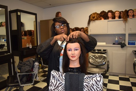 Working on a mannequin head of hair, junior Jasmine Black attends cosmetology class.