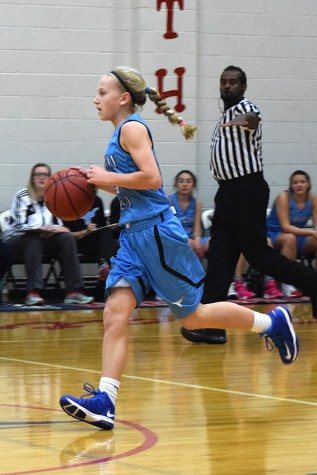 Dribbling down the court, freshman Tess Allgeyer looks for a player to make a pass.