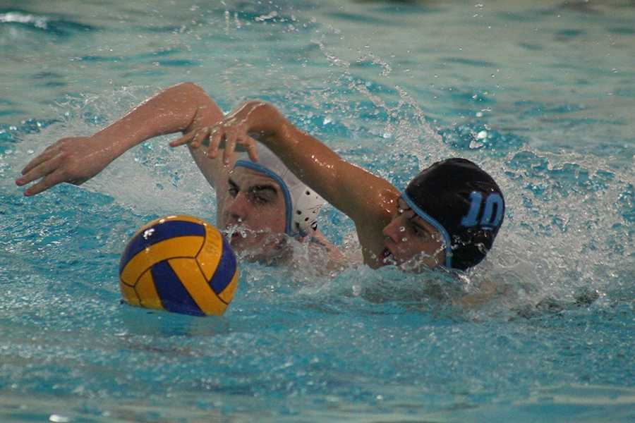 Sophomore Paris Wilken and freshman Ryan Mendonsa swim for the ball as part of their preparation during water polo practice.