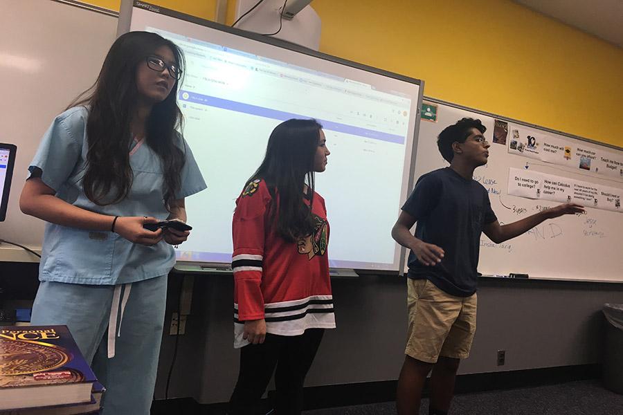 Junior+Cheryl+Ma+and+sophomore+Gokul+Venkatachalam+performs+a+presentation+with+senior+Brooke+Ryan.