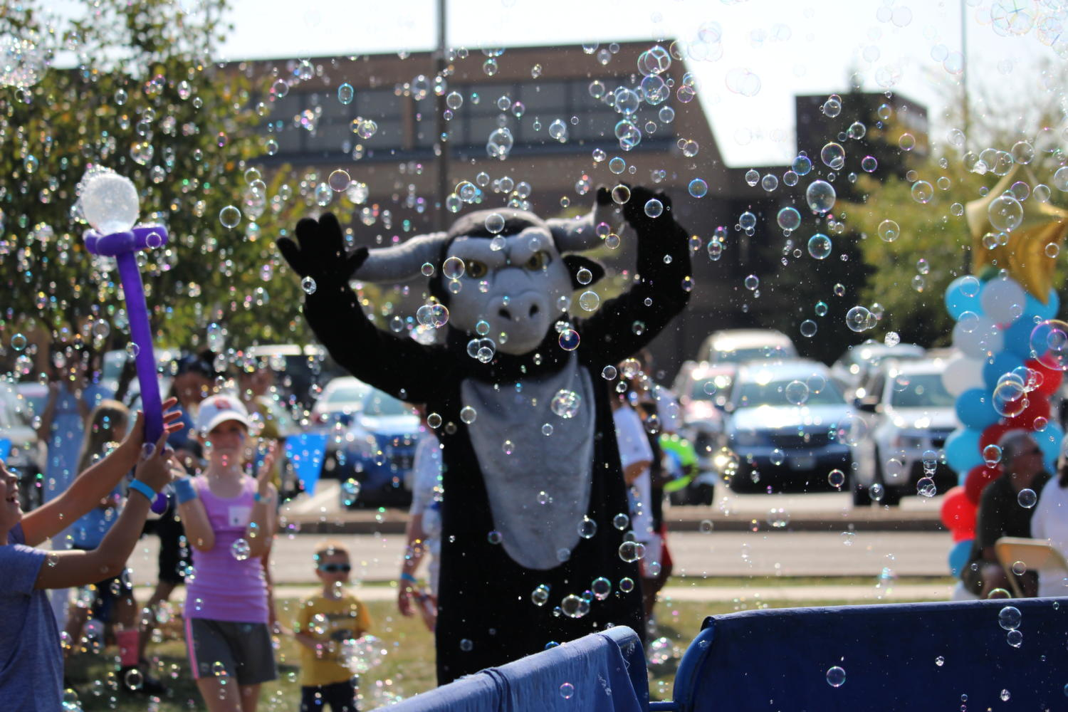 The school mascot poses in bubbles from a carnival bubble truck.