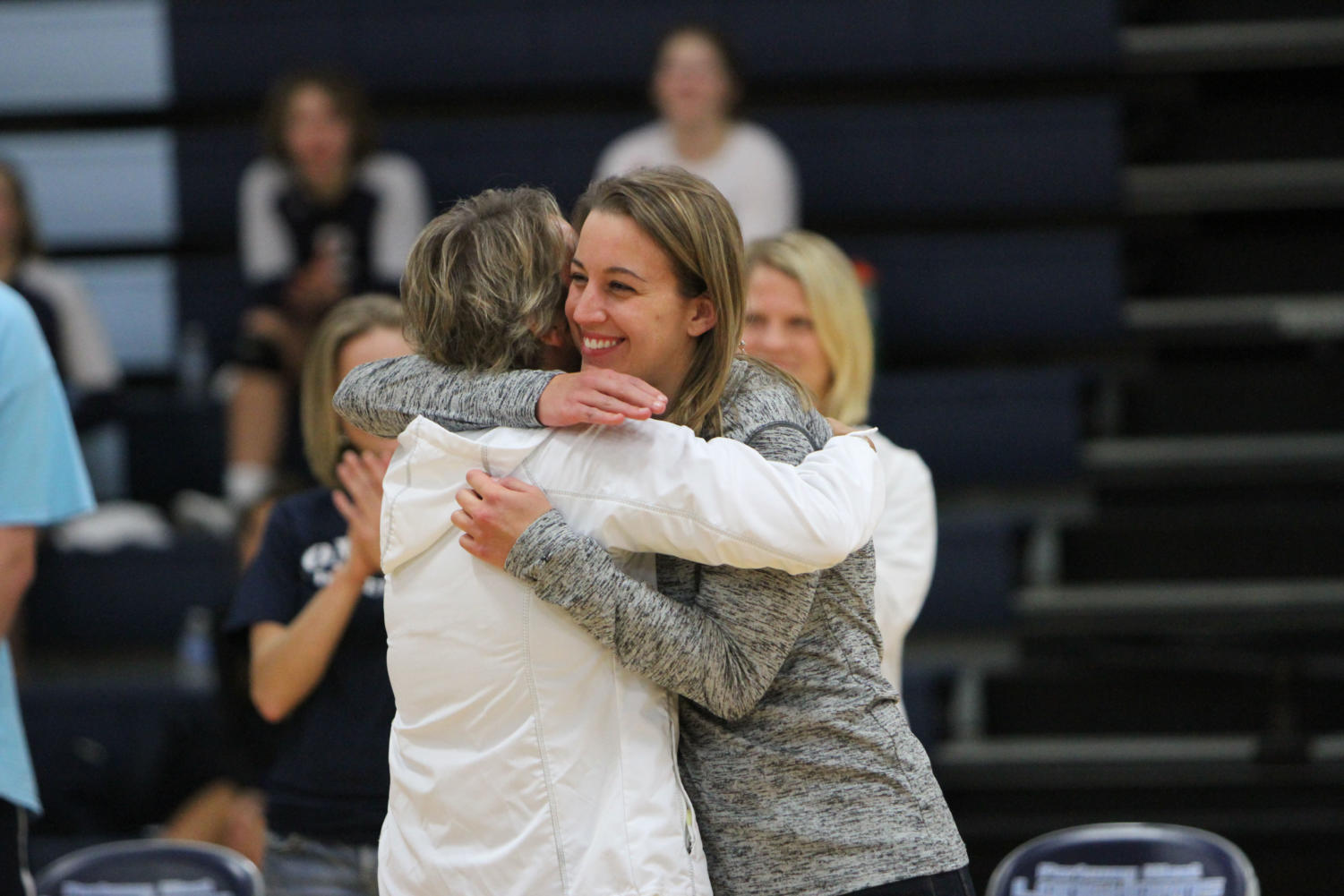 """Susan Dean hugs her 23-year-old daughter Molly Dean before the volleyball game against Webster Groves during the 2016-2017 season. The match ended in a victory for the Longhorns in two games, 25-18 and 27-25. """"The game was really special, in my mind that speaks for the tradition and longevity of our program,"""" Dean said."""