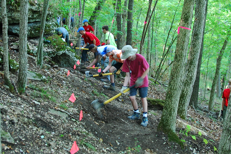 """During a workday, Adam Johnson and Boy Scout Troop 631 help Gateway Off-Road Cyclists  on the Rock Hollow trail in Wildwood. Trail builders use a variety of tools, like the """"pulaski"""" (axe-pick mix)."""