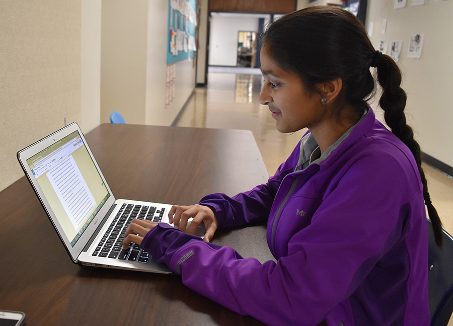"""Typing on her laptop, Shah looks over the work she has done. Her research surrounds ophthalmology, and she has worked with graduate students studying the effect of the eclipse on retinas. """"I got involved because my dad got me in contact with a few people, but then I reached out to more people at [Washington University] to see if I could help them work,"""" Shah said."""