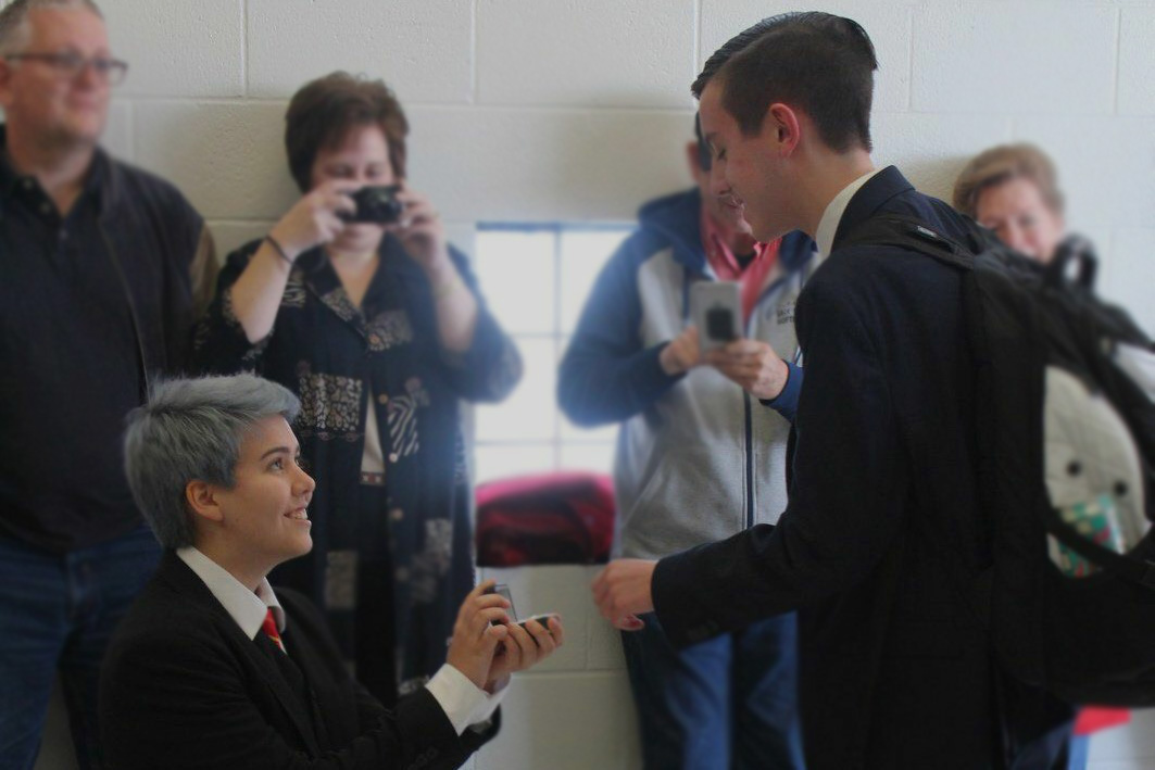 """Senior Charlie Woodruff bends down on one knee to propose. All the members of the speech and debate team and family on both sides were at Marquette to see Woodruff propose to Senior Victor Folk. """"It was an emotional spectacle to watch. People on the team were getting teary eyed, and we were all so happy for them, """" senior Haran Kumar said."""
